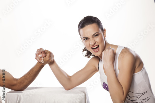 happy girl with winning gesture wrestles hand with men