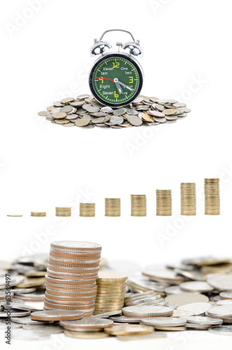 Alarm clock standing with coins isolated on white background