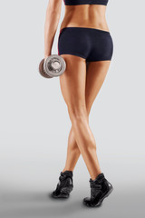 Shapely female legs in sporting black shorts. Fitness.