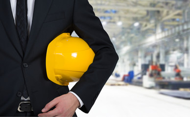 Businessman holding a yellow cap.