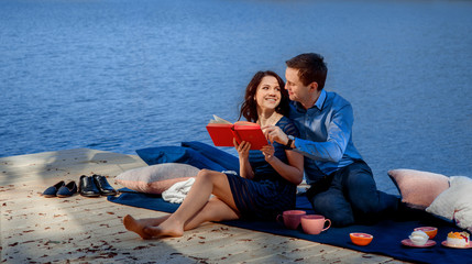 couple sitting and reading on terrace near the water