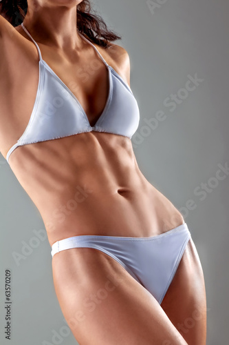 athletic woman in a white bathing suit. abdominal muscles