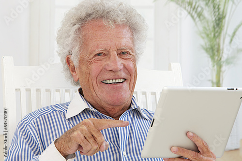 Smiling Elderly man with electronic tablet