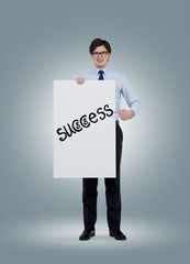 Businessman holding a poster with the word 'success'