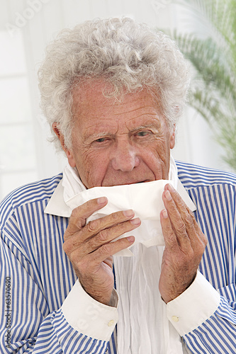 Senior man with white hair  having a cold , sneezing