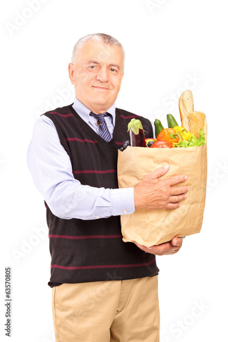 Mature man holding a bag full of groceries