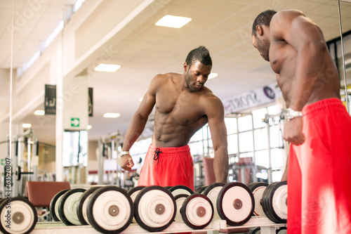 Strong black man exercising with dumbbells in the gym.