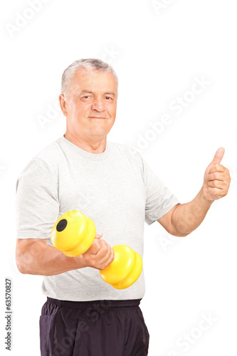 Mature man lifting a dumbbell and giving thumb up