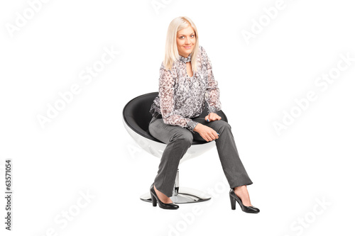 Trendy woman sitting on a modern chair