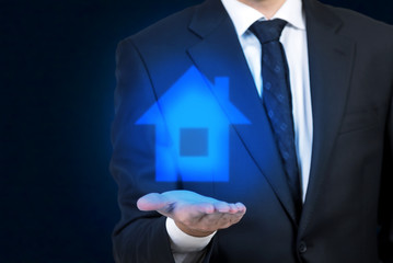 Businessman holding a hologram house icon