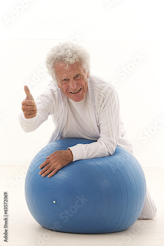 senior man holding thumb up on gym ball