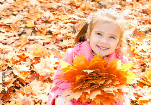 Autumn portrait of cute smiling little girl with maple leaves