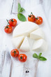 Sliced adygea cheese, baked tomatoes and mint leaves