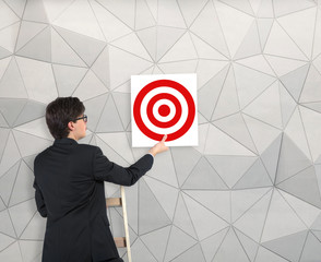 Businessman hanging up the target