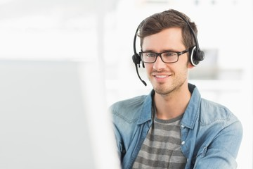 Smiling casual young man with headset using computer