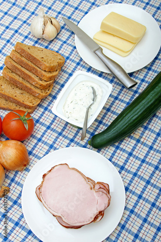 table with fresh vegetables, meat, cheese and bread