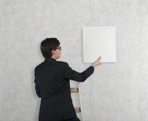 Businessman hanging up the blank picture