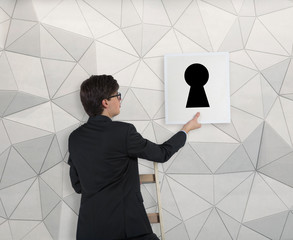 Businessman hanging up the picture of the keyhole