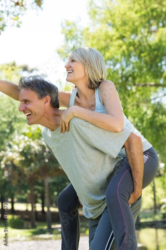 Couple enjoying piggyback ride in park