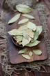 Dried bay leaves on a wooden chopping board, vertical shot