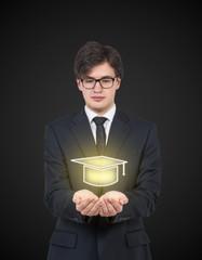 Businessman holding a graduation hat.