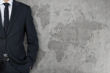 Businessman and world background wall (grey, concrete)