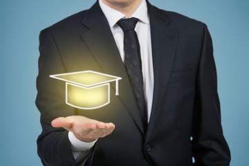 Businessman holding a graduation hat.