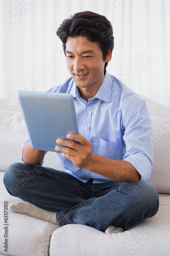 Happy man sitting on couch using tablet pc