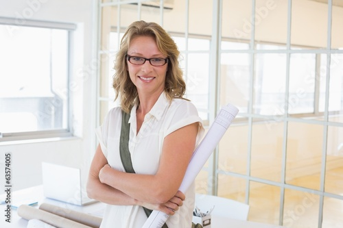 Casual architect smiling at camera holding blueprint