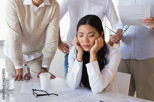 Stressed casual businesswoman surrounded by peers