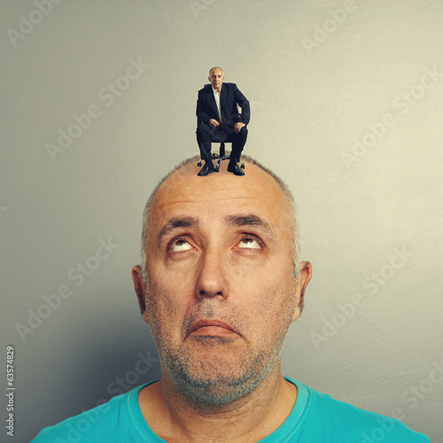 amazed man looking up at calm businessman
