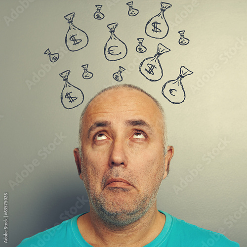 senior man looking up at bags with money