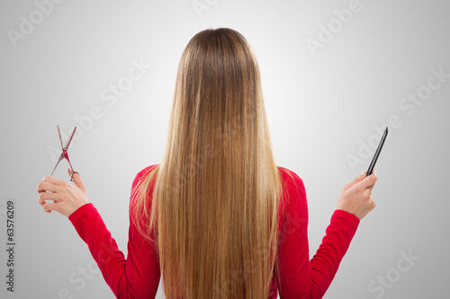Woman holding comb and scissors