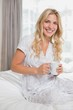 canvas print picture - Beautiful casual woman holding coffee cup in bed