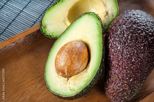 Ripe halved avocado on plate. Indoors closeup.