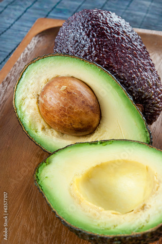 Ripe avocado on wooden plate. Indoors closeup.
