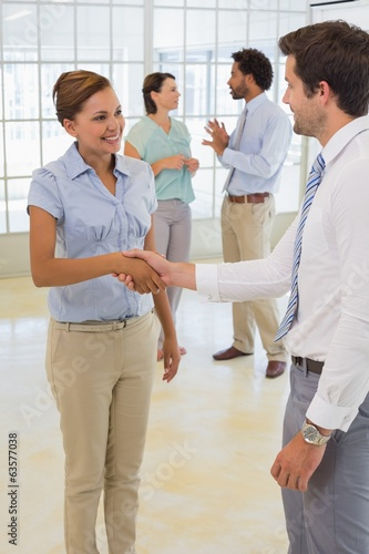 Business people shaking hands with colleagues at office