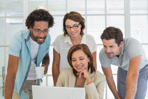 Smiling business people using laptop together