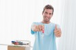 Man holding out new house key while gesturing thumbs up