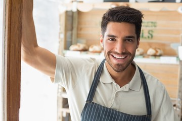 Smiling confident male barista at coffee shop