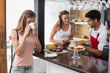 Woman drinking coffee with friend and male barista in coffee sho