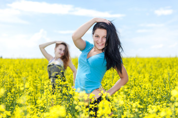 Two women in agricultural fields. Yellow flowers.