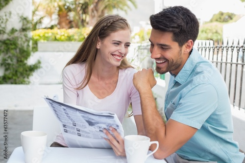 Smiling couple reading newspaper at café