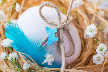 Easter rustic decorated egg in nest and spring flowers.