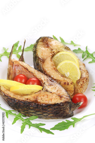 Grilled carp steaks with herbs and lemon.