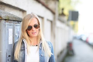 Blonde Frau im Sommer mit Jeansjacke