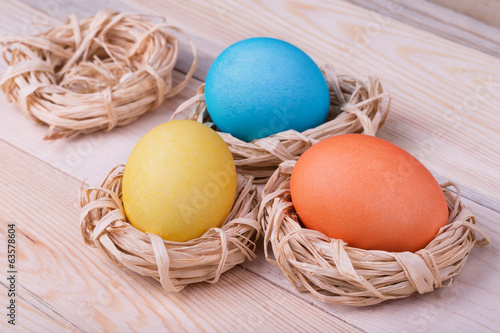 Three colored eggs in small nests