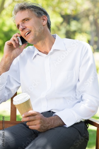 Businessman using cell phone at park