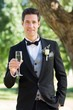 Sophisticated groom holding champagne flute in garden