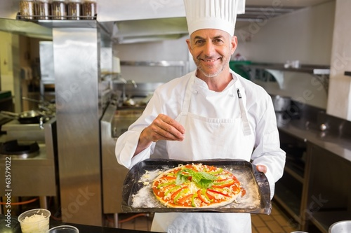 Confident male chef holding cooked food in kitchen